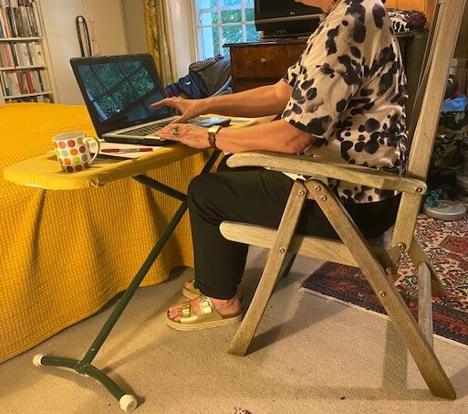 Home office - woman sat in garden chair with laptop on ironing board