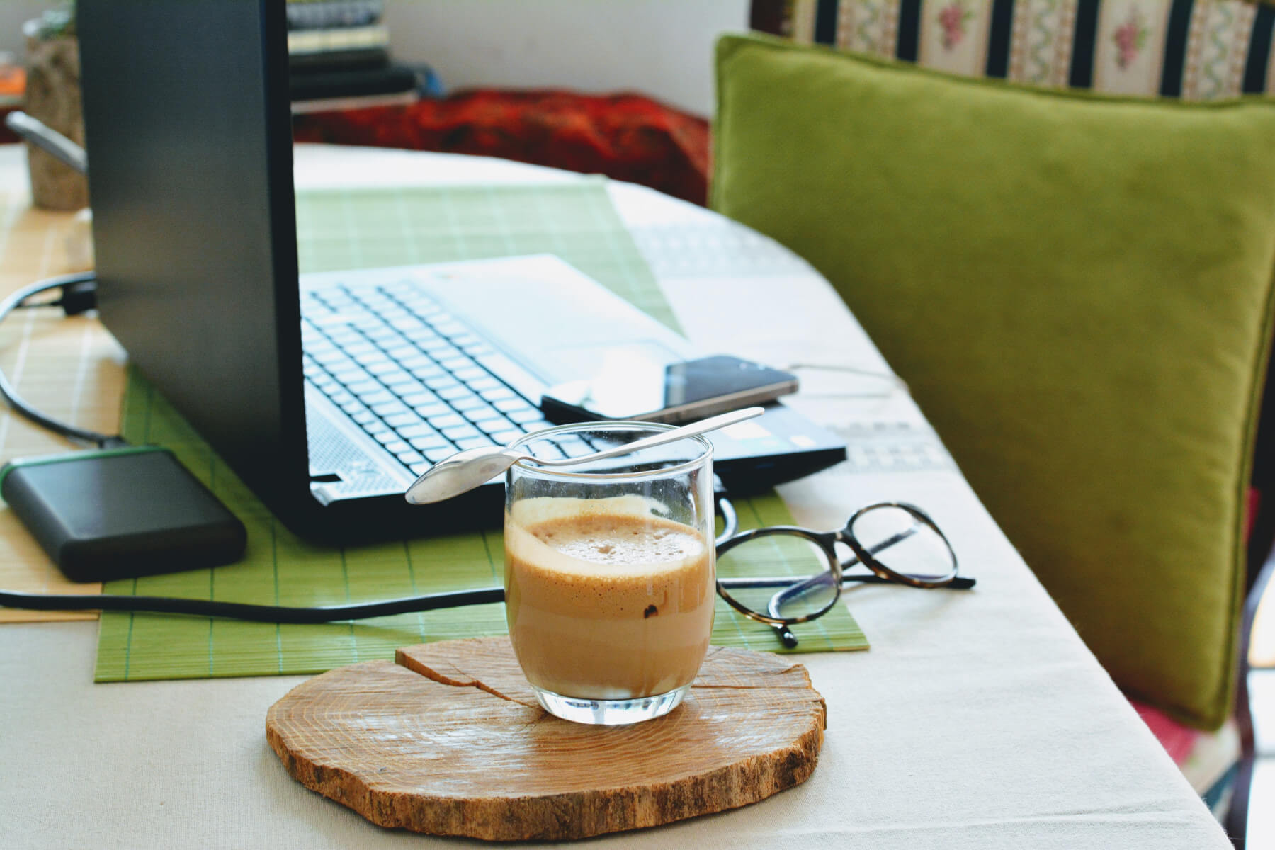 Working from home - cup of coffee on table beside laptop